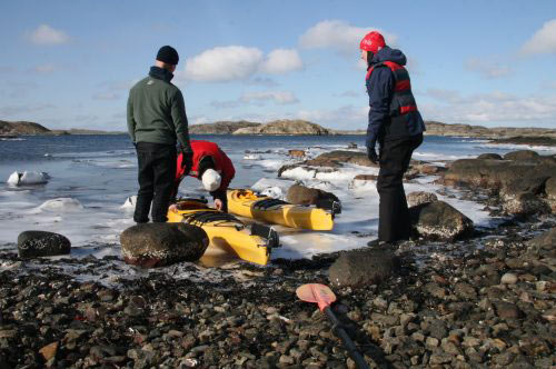 active guests prepare their kayaks for a paddle tour in wintertime