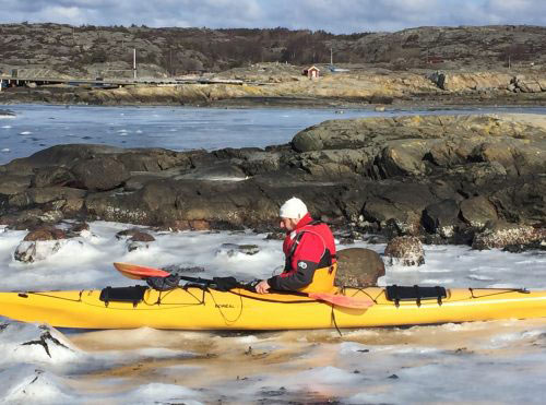 guest of Lådfabriken is paddling out in a kayak through an icy sea during wintertime